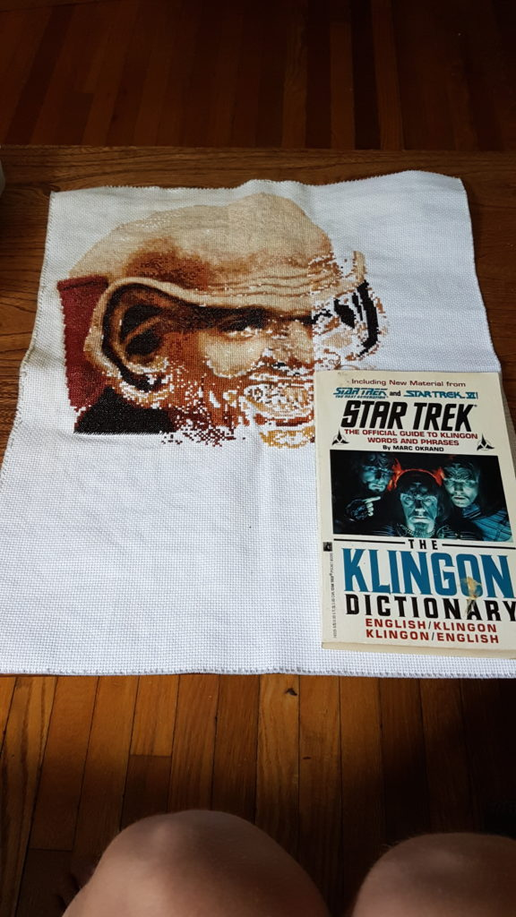 A half-finished portrait of Nog from Deep Space Nine with a copy of The Klingon Dictionary on top.