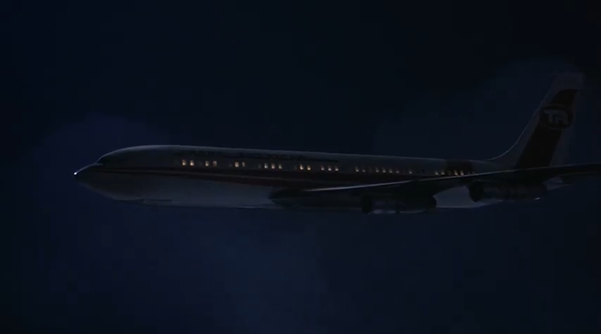 In a still from the film Airplane!, a passenger plane flies through the clouds at night.