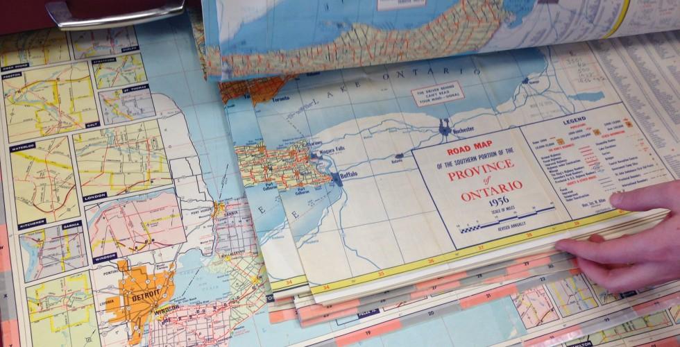 Jordan's hands flipping through a drawer of historic Ontario highway maps